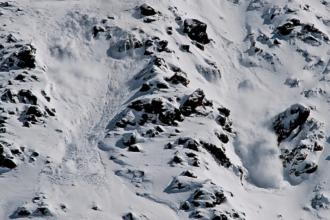 Medium-sized avalanches on the East Wall at Arapaho Basin Ski Area, Colorado triggered by the ski patrol are marked by clouds of snow dust. Credit: Bob Berwyn