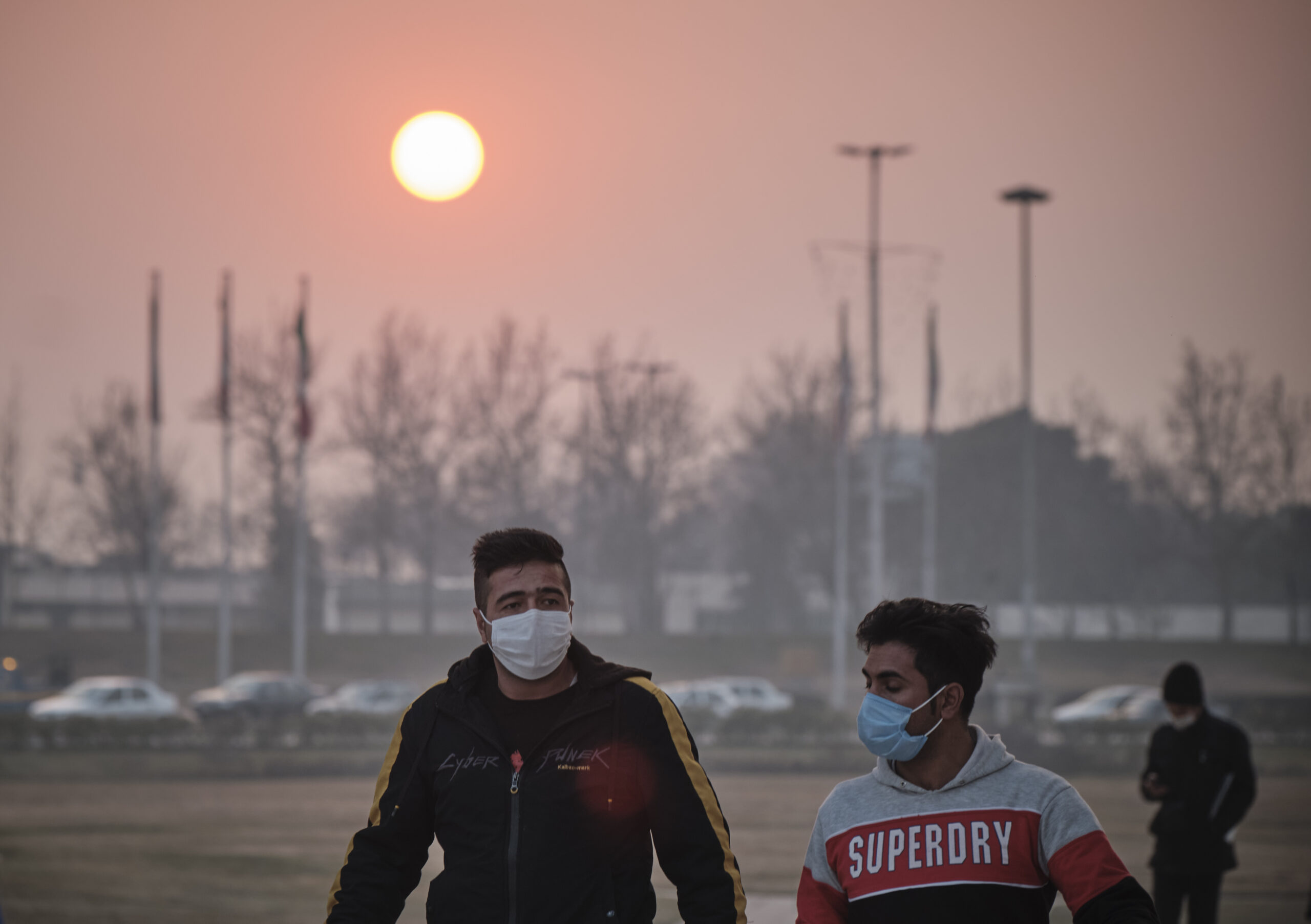 Two Iranian men wearing protective face masks walk along the Azadi (Freedom) Square in western Tehran during a polluted air, following the Covid-19 outbreak in Iran, on January 12, 2021. Credit: Morteza Nikoubazl/NurPhoto via Getty Images