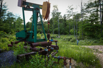 Laurie Barr, co-founder of Save Our Steams Pennsylvania, searches abandoned oil wells for pollutants as an old pumpjack stands in the Allegeny National Forest near Marienville, Pennsylvania, on Monday, June 6, 2016. Credit: Chris Goodney/Bloomberg via Getty Images