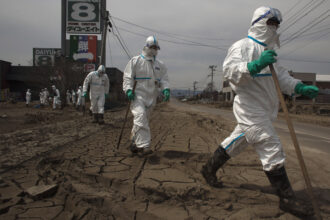 Japanese Police wearing protective suits search for tsunami victims about 12 miles away from Fukushima Nuclear Power Plant on April 7, 2011 in Minamisoma, Fukushima Prefecture, Japan. Credit: Athit Perawongmetha/Getty Images