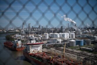 Ships are docked along refinery facilities at the Houston Ship Channel, part of the Port of Houston, on March 6, 2019 in Houston, Texas. Credit: Loren Elliot/AFP via Getty Images