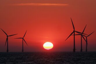 The sun starts to rise behind Britain's largest offshore wind farm on July 19, 2006 in Norfolk, England. Credit: Matt Cardy/Getty Images