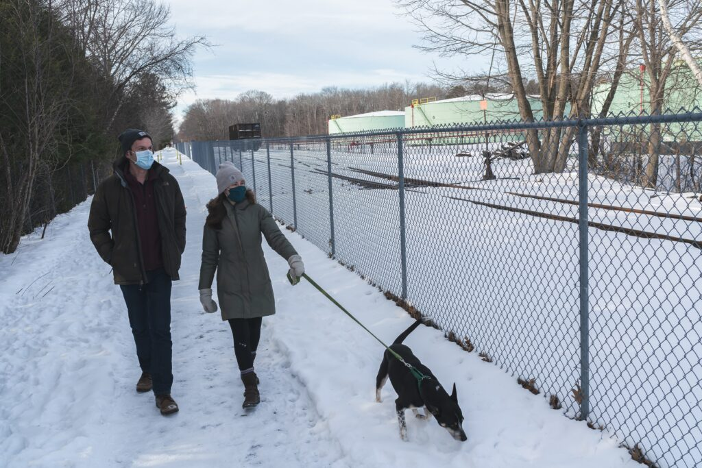 Rob e Brittany Liscord caminham com seu cachorro, Arlo, ao longo da Greenbelt Walkway em seu bairro em South Portland, Maine em 13 de fevereiro. Os Liscords vivem a um décimo de milha de tanques de armazenamento (ao fundo) de propriedade da Global Partners, um empresa de energia que usa seus tanques para armazenar produtos petrolíferos.  Rob Liscord disse que às vezes fica com dor de cabeça depois de correr e ambos se preocupam como a qualidade do ar em sua vizinhança está afetando sua saúde.  Crédito: Yoon S. Byun