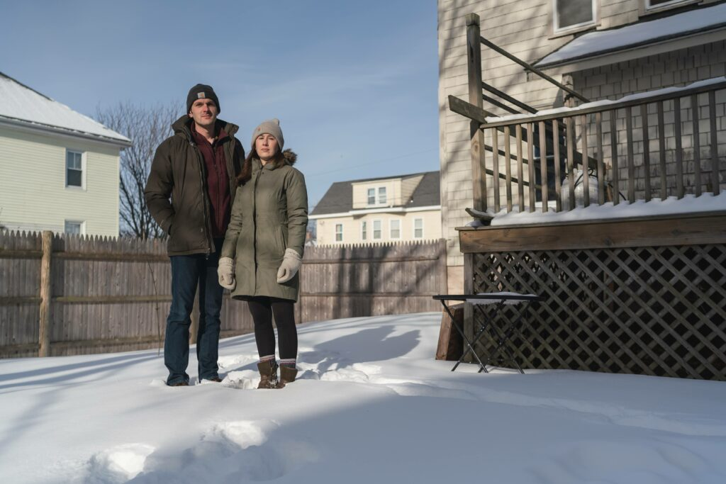 Rob and Brittany Liscord are photographed with their dog, Arlo, in their backyard in South Portland, Maine on Saturday, Feb. 13, 2021. The Liscords live one-tenth of a mile from storage tanks owned by Global Partners, an energy company that uses its tanks to store petroleum products. Global Partners and Sprague Resources, also located in South Portland, have settled lawsuits in recent years with the EPA for violating the Clean Air Act due to the high level of VOCs coming from their tanks. Credit: Yoon S. Byun