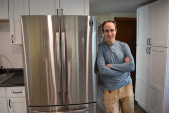 Phil McKenna poses with his new, HFC-free refrigerator. Courtesy of Phil McKenna
