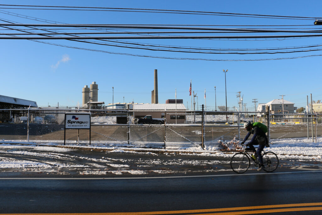A cyclist passes Sprague's Everett terminal, located across the street from a group of homes. Credit: Julia Kane/Inside Climate News