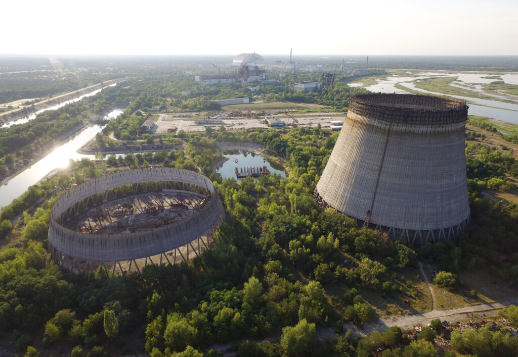 In this aerial view, abandoned, partially-completed cooling towers stand at the Chernobyl nuclear power plant as the new, giant enclosure that covers devastated reactor No. 4 stands behind on Aug. 18, 2017 near Chernobyl, Ukraine. On April 26, 1986 reactor number four exploded after a safety test went wrong, spreading radiation over thousands of square kilometers in different directions. Credit: Sean Gallup/Getty Images