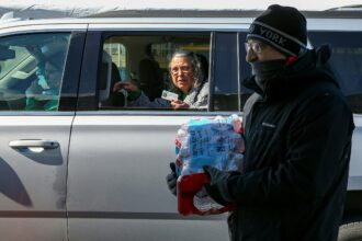 Volunteers hand out cases of water bottles to Galveston residents at the Schlitterbahn Waterpark parking lot on Feb. 19, 2021 in Galveston, Texas. Credit: Thomas Shea/AFP via Getty Images