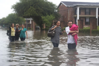 People walk down a flooded street as they evacuate their homes after the area was inundated with flooding from Hurricane Harvey on August 27, 2017 in Houston, Texas. Credit: Joe Raedle/Getty Images