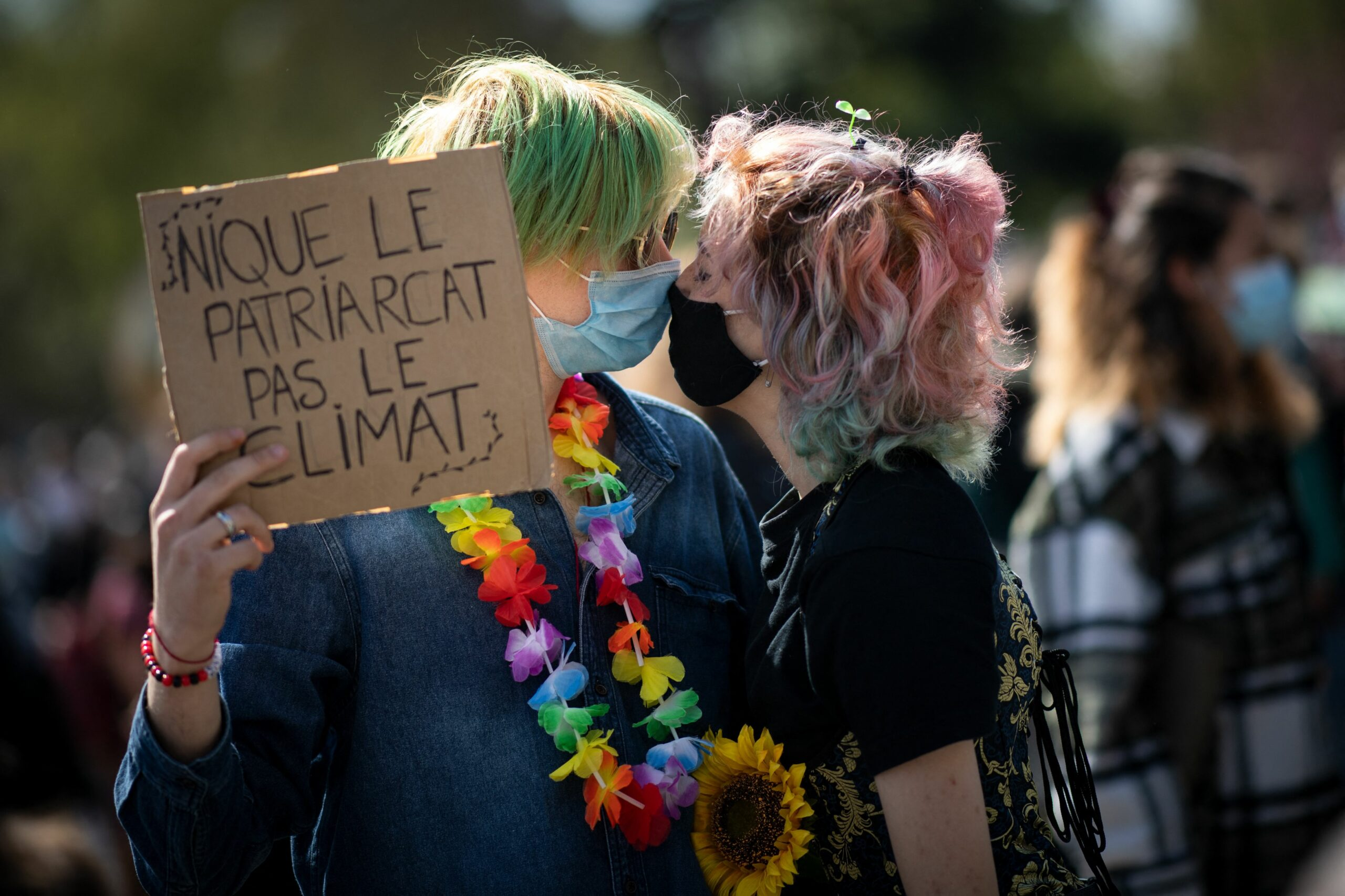 """Demonstrators kiss with their protective face masks, as they hold a placard reading """"down with the patriarchy, not the climate"""", during a demonstration called by youth for climate and several NGOs and unions for a """"true"""" law on climate, in Nantes, western France, on March 28, 2021. Credit: Loic Venance/AFP via Getty Images"""