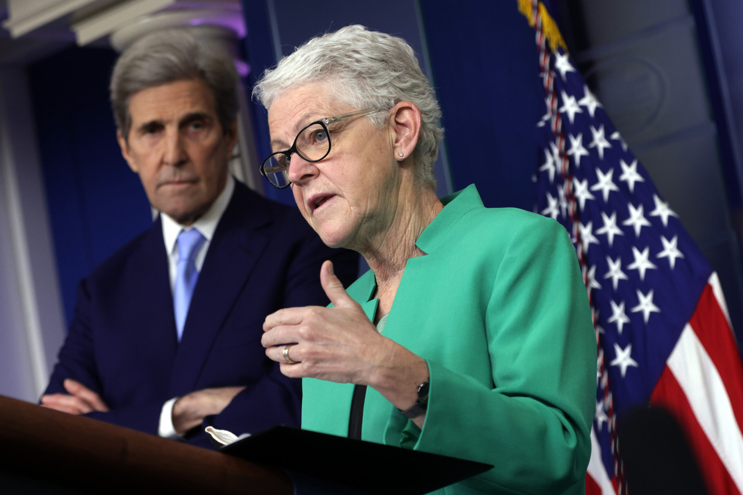 National Climate Adviser Gina McCarthy speaks as Special Presidential Envoy for Climate and former Secretary of State John Kerry listens during a daily press briefing at the James Brady Press Briefing Room of the White House on April 22, 2021 in Washington, DC. Credit: Alex Wong/Getty Images