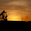An oil well jack pump and natural gas flare off at sunset in the Bakken oil field north of Williston, North Dakota. Credit: William Campbell/Corbis via Getty Images