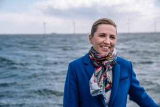 Denmark's Prime Minister Mette Frederiksen smiles as she stands on a boat with wind turbines of the Middelgrunden offshore wind farm in the background, in Oeresund between Denmark and Sweden, outside Copenhagen, on April 22, 2021. Credit: Emil Helms/Ritzau Scanpix/AFP via Getty Images