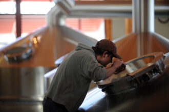 A New Belgium brewer Andrew checks the water level of sparge bath at the brewery Credit: Hyoung Chang/The Denver Post via Getty Images