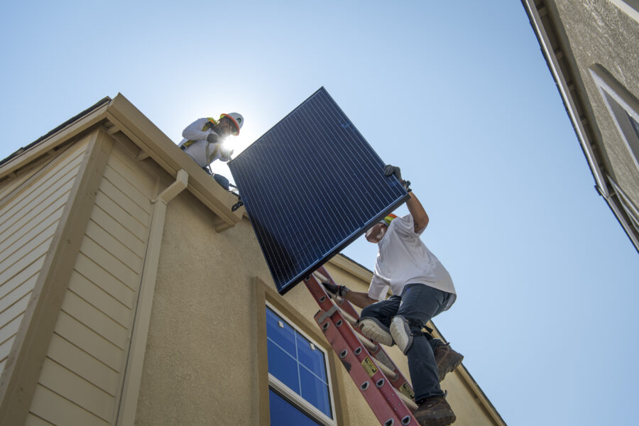 Contractors move a SunRun Inc. solar panel up a ladder to the roof of a new home at the Westline Homes Willowood Cottages community in Sacramento, California, on Wednesday, Aug. 15, 2018. Credit: David Paul Morris/Bloomberg via Getty Images