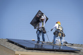Contractors install SunRun Inc. solar panels on the roof of a new home at the Westline Homes Willowood Cottages community in Sacramento, California, on Aug. 15, 2018. Credit: David Paul Morris/Bloomberg via Getty Images
