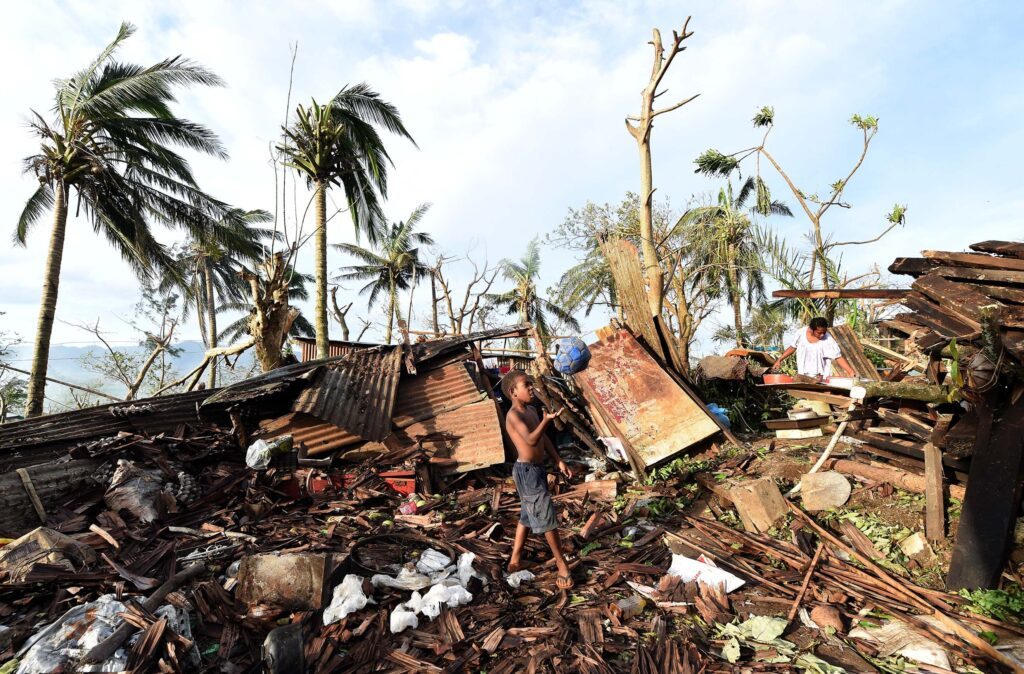 A young boy plays with a ball as his mother searches through the ruins of their family home on March 16, 2015 in Port Vila, Vanuatu. Cyclone Pam hit South Pacific islands in 2015 with hurricane force winds, huge ocean swells and flash flooding and caused severe damage. Credit: Dave Hunt-Pool/Getty Images
