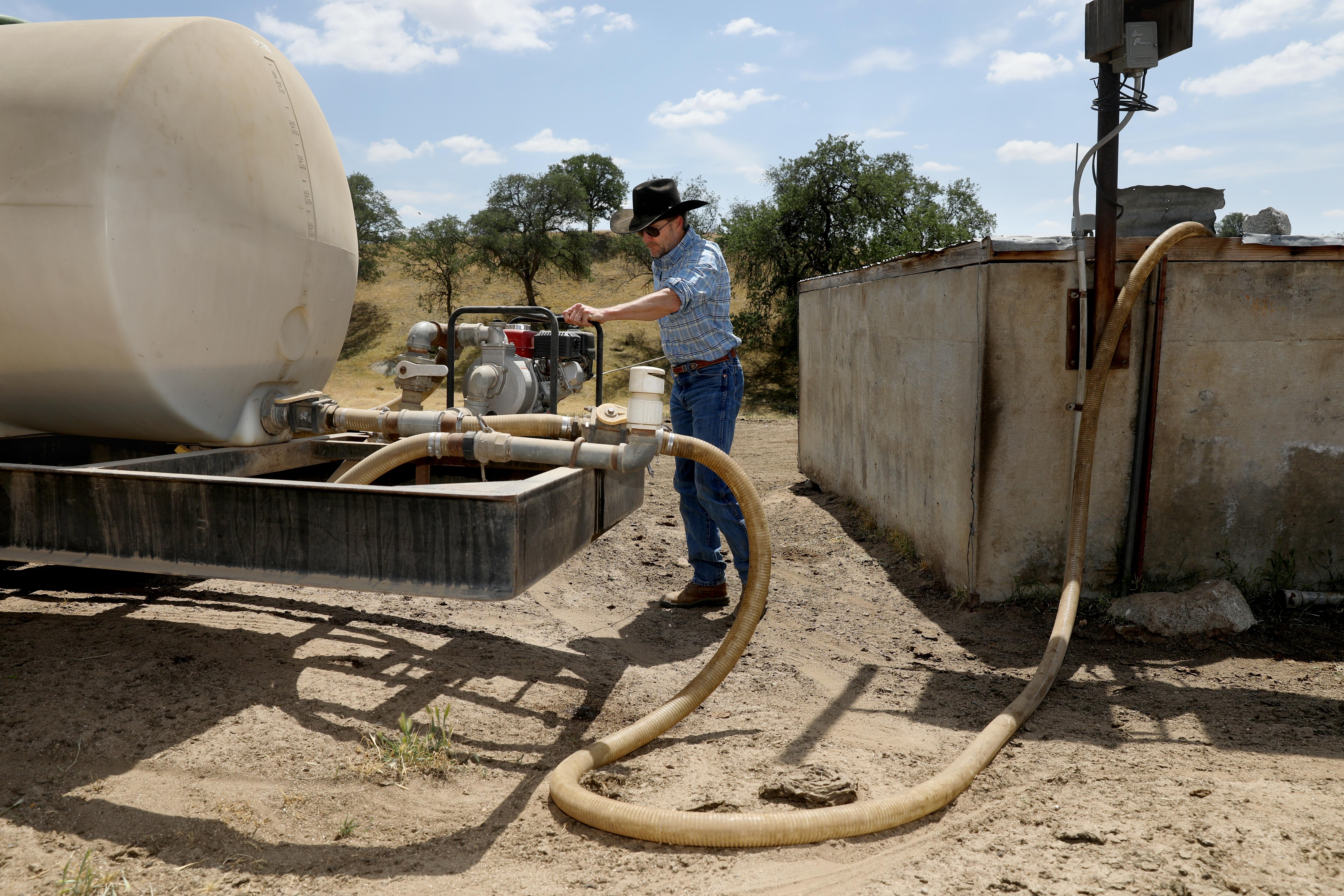 John Guthrie, 52 ans, président du Tulare County Farm Bureau et propriétaire d'un élevage et d'une ferme qui appartient à sa famille depuis 150 ans, pompe l'eau d'une citerne de 3000 gallons dans une remorque à eau pour la ramener au siège de son ranch dans le sud-est. Comté de Tulare le jeudi 22 avril 2021 à Porterville, Californie. Crédit: Gary Coronado / Los Angeles Times via Getty Images