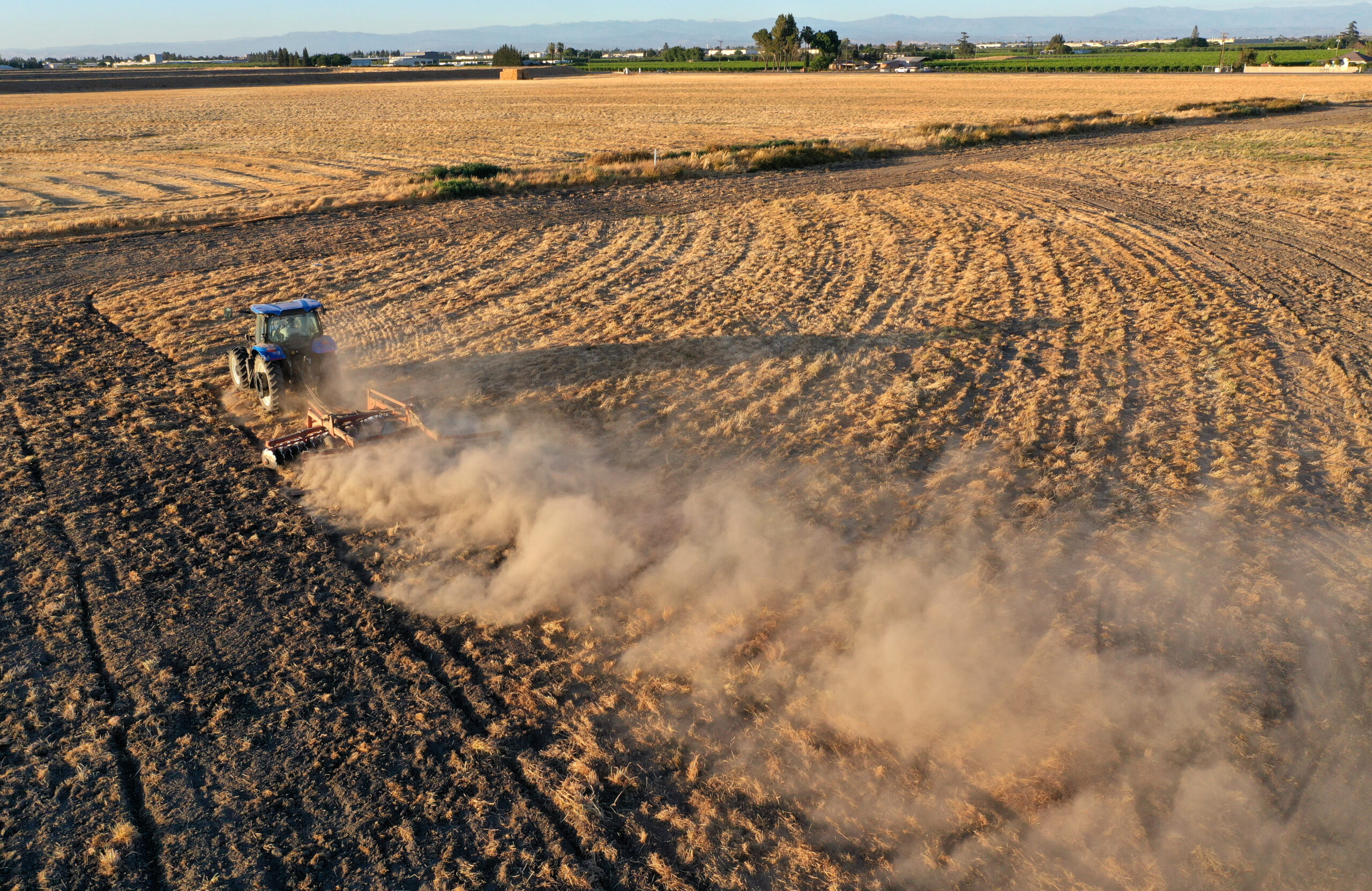 In an aerial view, a tractor kicks up dust as it plows a dry field on May 25, 2021 in Madera, California. As California enters an extreme drought emergency, water is starting to become scarce in California's Central Valley. Credit: Justin Sullivan/Getty Images