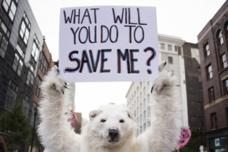 A climate protester holds up a placard in Cleveland, Ohio, on July 18, 2016. Credit: Jim Watson/AFP via Getty Images