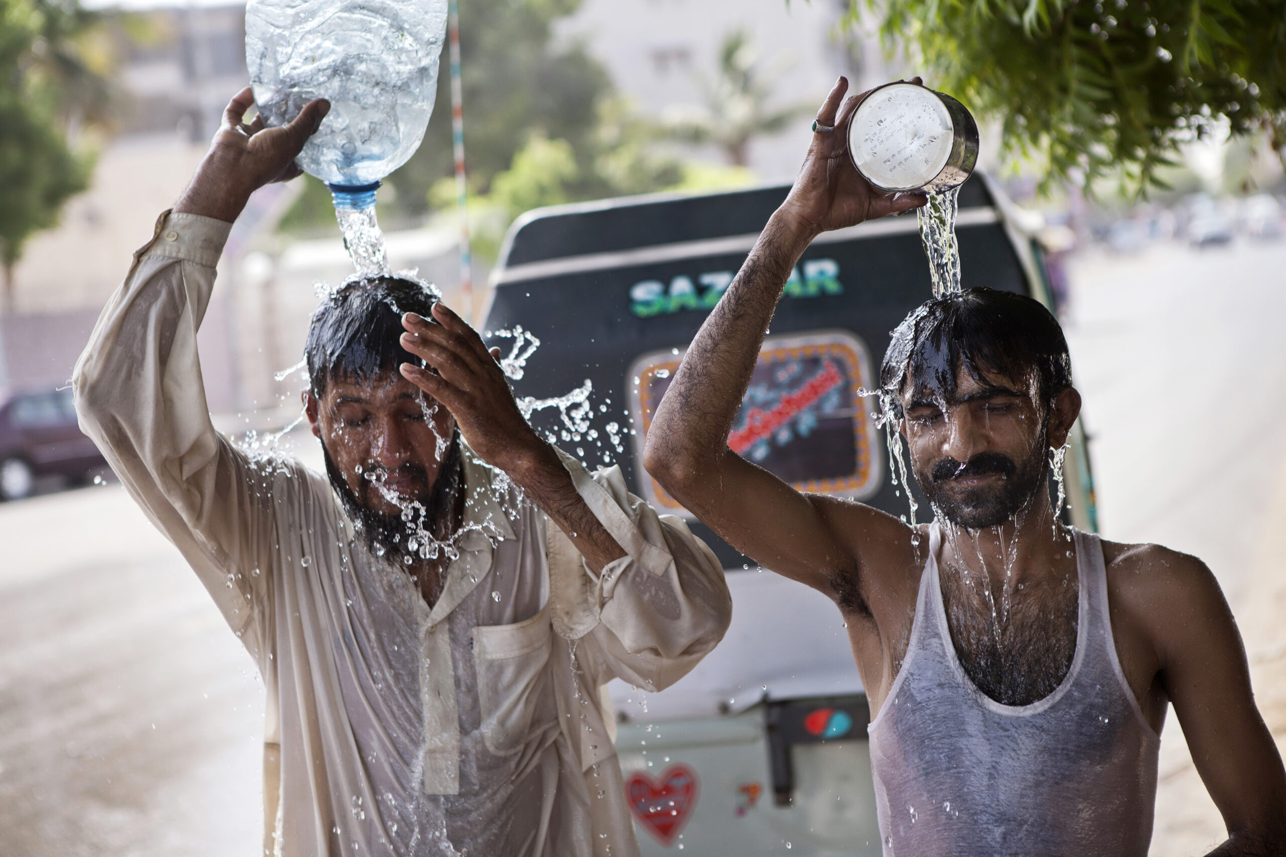 People pour water over themselves at a broken water pipe during a heat wave in Karachi, Pakistan on June 29, 2015. Credit: Asim Afeez/Bloomberg via Getty Images