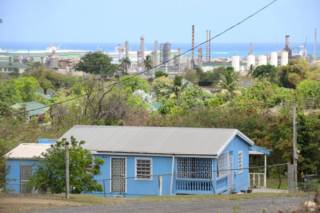 The St. Croix neighborhood of Clifton Hill overlooks a quieted Limetree Bay Refinery on Tuesday, May 25 after a stack fire and massive oil flare caused a 60-day shutdown ordered by the U.S. Environmental Protection Agency. Clifton Hill residents, many of whom migrated to St. Croix from nearby Vieques, are no strangers to the refinery's discharges under its previous owner, Hovensa. But the most recent shower of oil on their homes, cars, gardens and cisterns was the second in little over three months as the beleaguered 60-year-old refinery struggled to resume operations after an eight-year hiatus. Credit: Patricia Borns