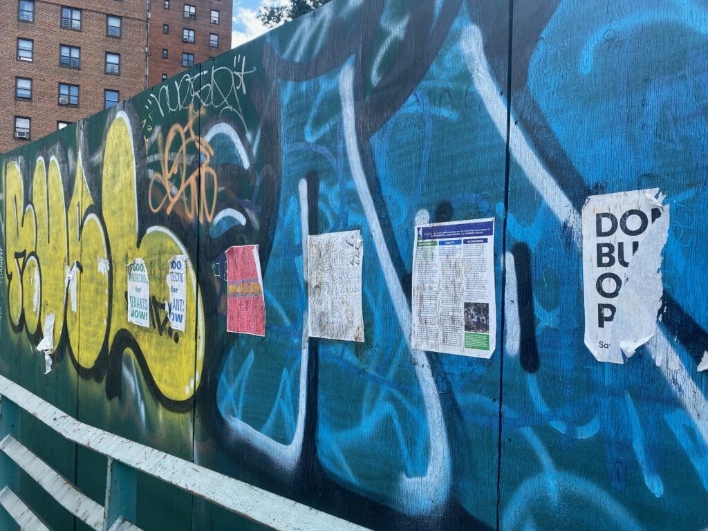 Graffiti and opposition signs for the construction of the new East River Park hang on East 6th Street along FDR Drive in Lower Manhattan. Credit: Brahmjot Kaur/Inside Climate News