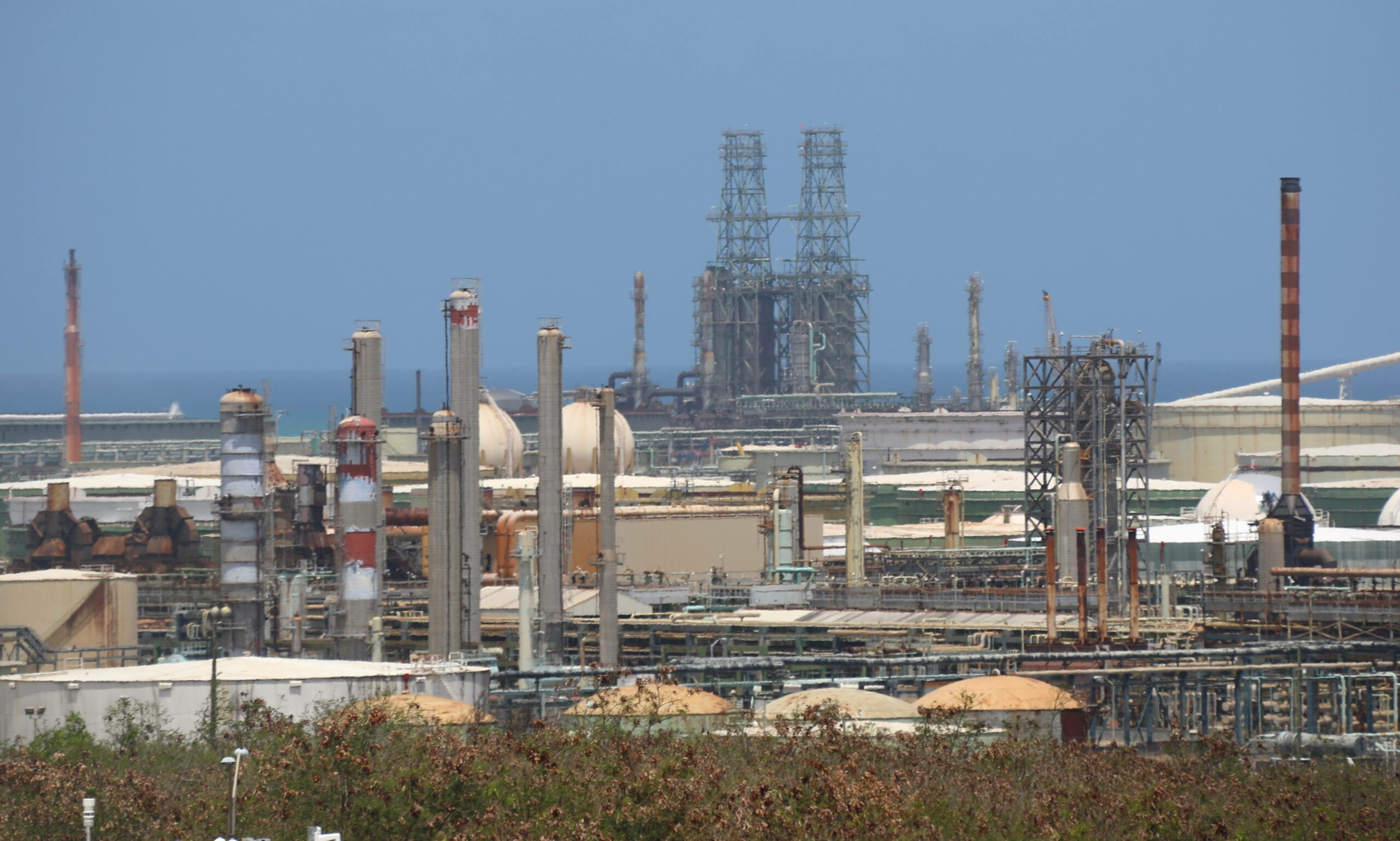 The twin towers of the coker at the sprawling Limetree Bay refinery in St. Croix. Since February when the refinery restarted after an eight-year hiatus, problems with the coker and other processing units have created massive amounts of pressure inside the refinery, causing flares of oil and toxic emissions that have sickened downwind neighbors within seven miles. Credit: Patricia Borns