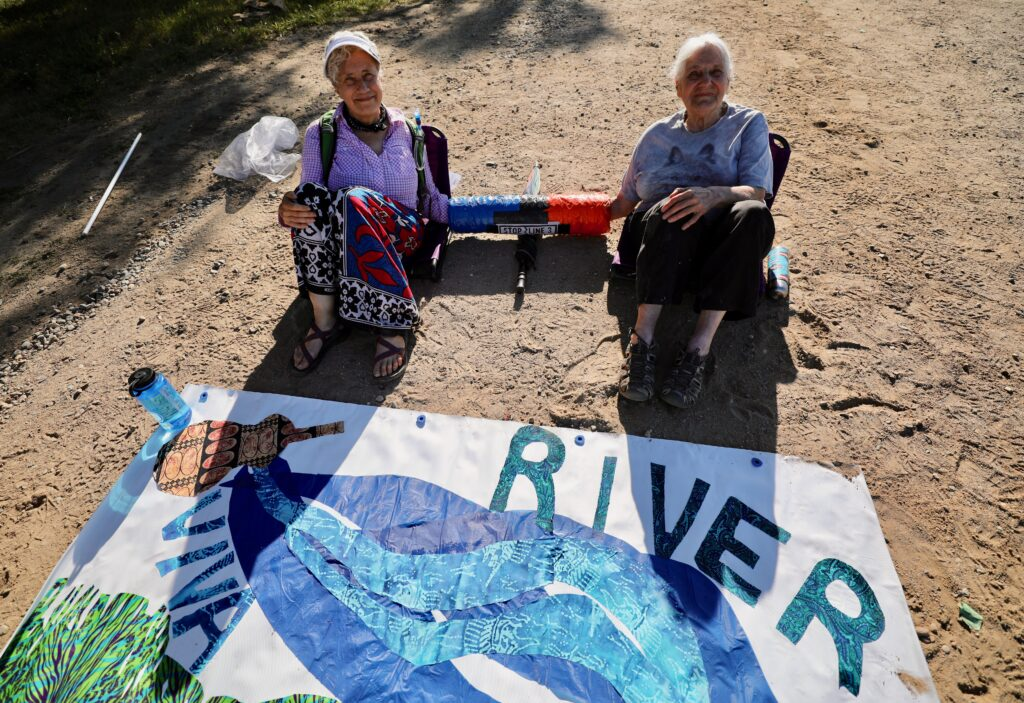 Minga Borne and Rema Loeb, both from Western Massachusetts chose one of the higher-risk direction actions and sat themselves in an access road to a Line 3 construction site near Park Rapids, Minnesota. Credit: Audrey Gray