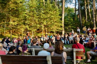 """Winona LaDuke welcomes a group of interfaith climate activists to Minnesota on Saturday night at the Northern Pines Camp near Park Rapids. """"Thank you for coming,"""" she said. """"It doesn't matter what color you are, you have to drink water."""" Credit: Audrey Gray"""