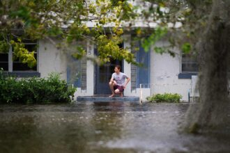 A man kneels on the top step of his porch as he looks out over the flooded streets of the San Marco historic district of Jacksonville, Florida, on September 11, 2017, after storm surge from Hurricane Irma left the area flooded. Credit: Jim Watson/AFP via Getty Images