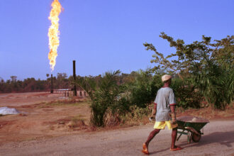 A villager walks past a column of fire from a natural gas flare station on March 8, 2001 near Akaraolu, Nigeria. Credit: Chris Hondros/Getty Images