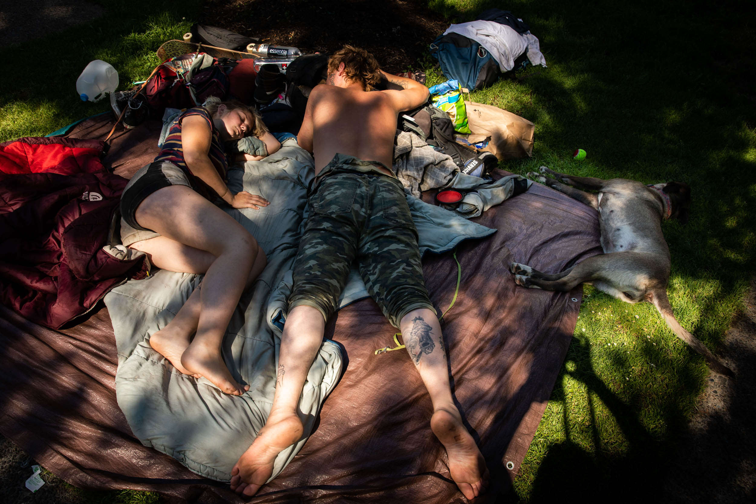 A couple and their dog lay in the shade during a heat wave in Portland, Oregon. on Monday, June 28, 2021. Credit: Maranie Staab/Bloomberg via Getty Images
