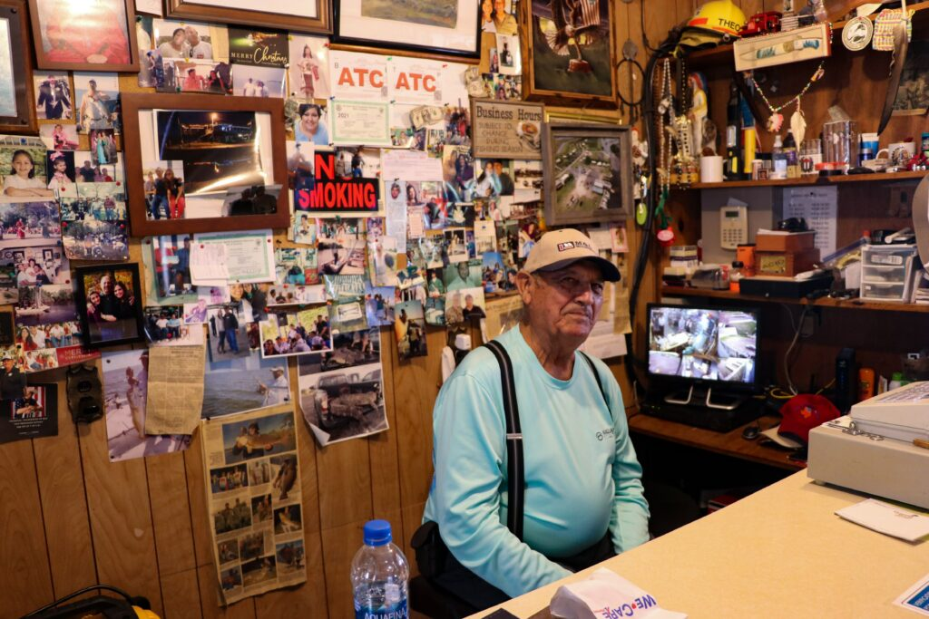 Theo Chaisson, a member of the United Houma Nation, greets customers at his shop on Isle de Jean Charles, one of the only businesses still open on the island. Credit: Katie Livingstone/Inside Climate News