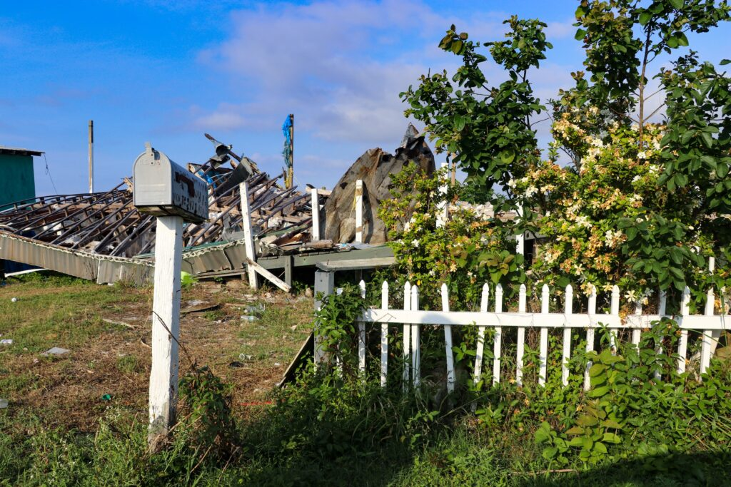 Destroyed by one of the frequent hurricanes to wreak havoc on the island in recent years, a mailbox and white picket fence surrounded by fragrant gardenias is all that remains of an Isle de Jean Charles home. Credit: Katie Livingstone/Inside Climate News