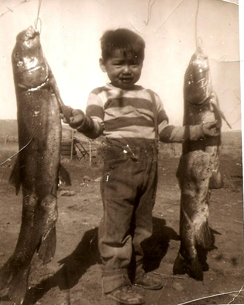 Glen Wilson, a young Klamath tribal member, stands with harvested fish in the early 1900s. Photo courtesy of the Klamath News Dept. and Monica YellowOwl