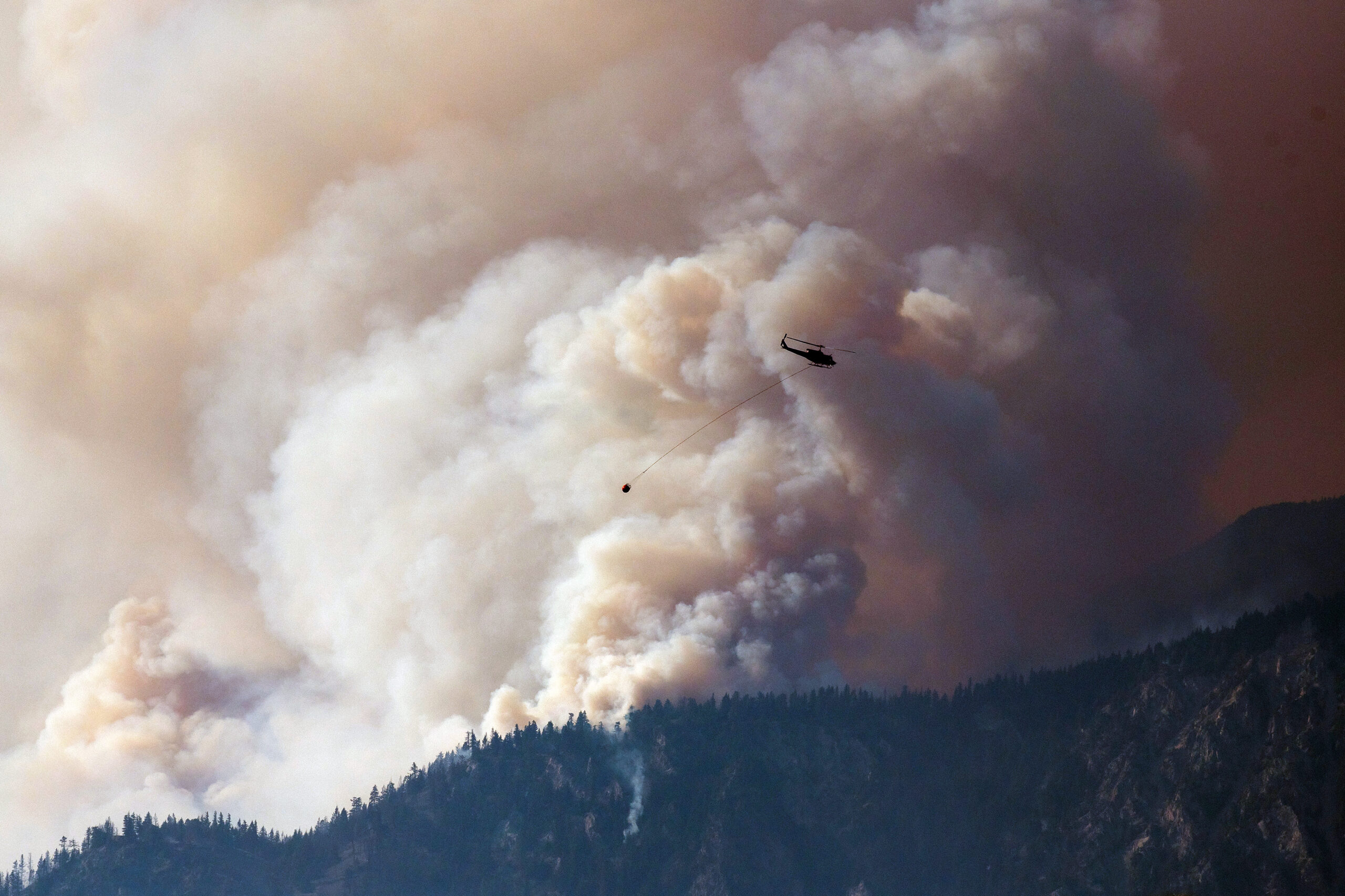 A helicopter prepares to make a water drop as smoke billows along the Fraser River Valley near Lytton, British Columbia, on July 2, as a protracted heat wave fueled scores of wildfires in Canada's western provinces. Credit: James MacDonald/Bloomberg via Getty Images