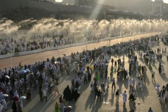 Prospective pilgrims walk on the road, which has water spray cooling system, to stone Jamarat pillars that symbolize the devil as a part of the annual Islamic Hajj pilgrimage during the first day of Eid Al-Adha in Mecca, Saudi Arabia on Sept. 2, 2017. Credit: Firat Yurdakul/Anadolu Agency/Getty Images