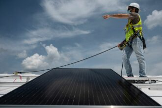 An employee with Ipsun Solar installs solar panels on the roof of the Peace Lutheran Church in Alexandria, Virginia on May 17, 2021. Credit: Andrew Caballero-Reynolds/AFP via Getty Images