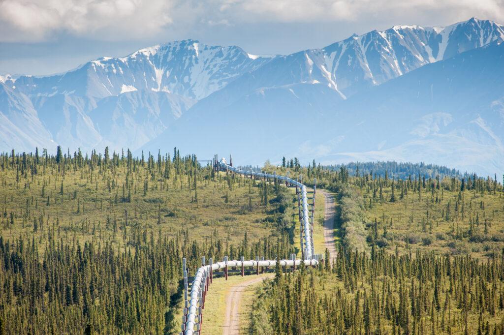 Trans-Alaska Pipeline (Alyeska pipleline) running through landscape with Mountain range in the distance in Alaska. Credit: Edwin Remsburg/VW Pics via Getty Images