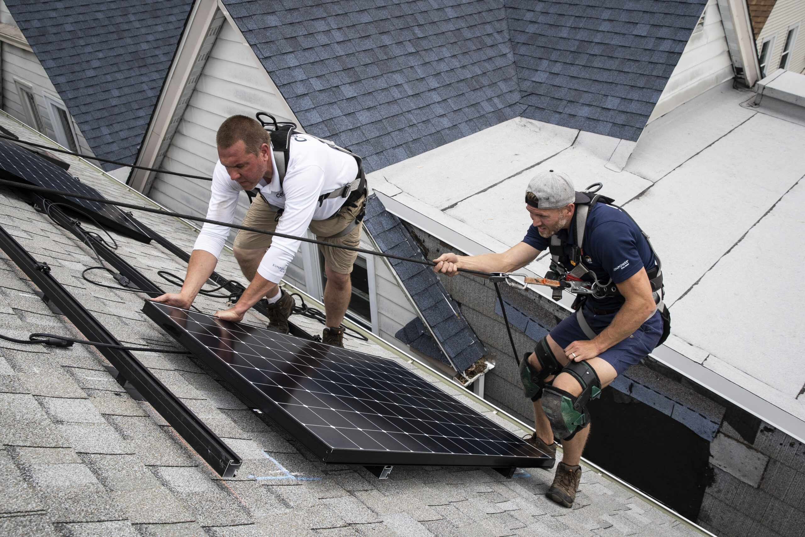 Pete Southerton (left) and Tom Bradshaw, of solar energy contractor Certasun, install solar panels on a Northwest Side home, Monday afternoon, May 17, 2021. Credit: Ashlee Rezin Garcia/Sun-Times