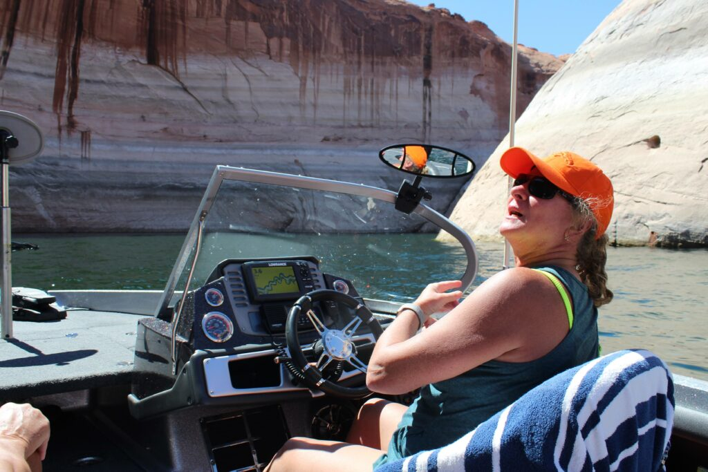 Sheri Facinelli steers a speedboat into a side canyon at Lake Powell. The reservoir is approaching its lowest level since it was built in the 1960s. Credit: Luke Runyon/KUNC