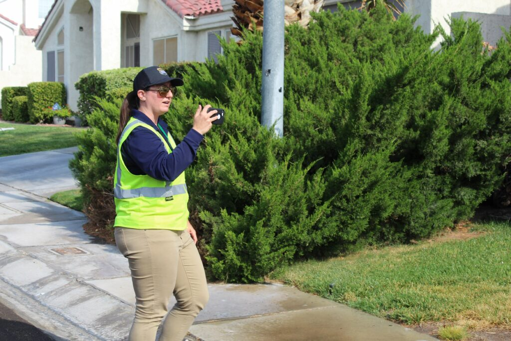 Devyn Choltko, a Las Vegas Valley Water District waste investigator, takes a video of irrigation water flowing into a storm drain. Credit: Luke Runyon/KUNC