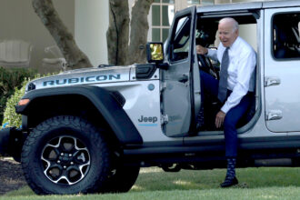 President Joe Biden climbs out of a Jeep Wrangler Rubicon Xe after driving it around the White House driveway following remarks during an event on the South Lawn of the White House on Aug. 5, 2021 in Washington, D.C. Biden delivered remarks on the administration's efforts to strengthen American leadership on clean cars and trucks. Credit: Win McNamee/Getty Images