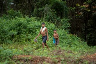 Arara indigenous children walk at the Arado tribal camp, in Arara indigenous land in Para state, Brazil on March 13, 2019. Credit: Mauro Pimentel/AFP via Getty Images