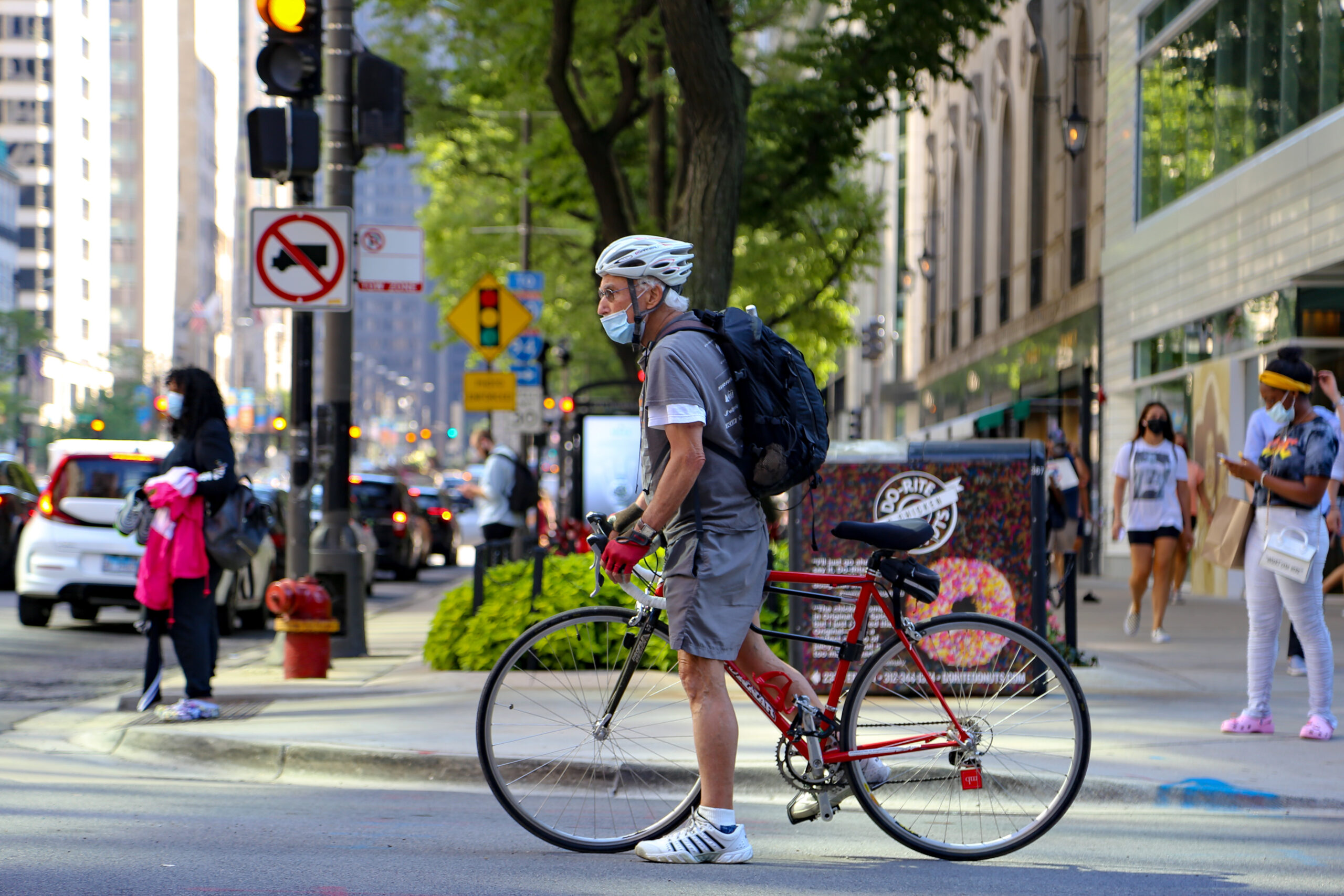 A bicyclist with a protective mask waits at an intersection along Michigan Avenue in Chicago, Illinois, on Friday, July 24, 2020. Credit: Olivia Obineme/Bloomberg via Getty Images