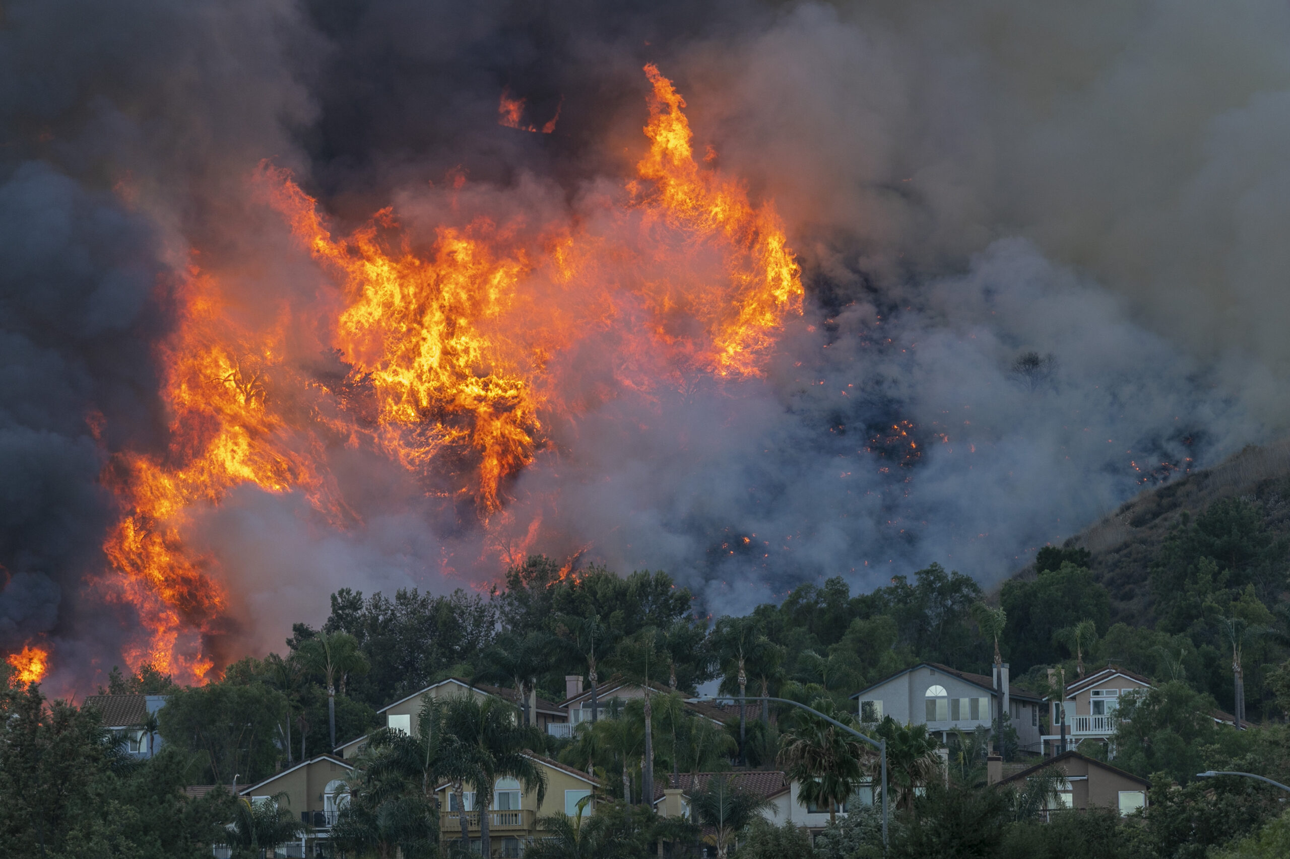 Flames rise near homes during the Blue Ridge Fire on Oct. 27, 2020 in Chino Hills, California. Credit: David McNew/Getty Images