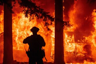 Firefighters try to get control of the scene as the Dixie fire burns dozens of homes in the Indian Falls neighborhood of unincorporated Plumas County, California on July 24, 2021. Credit: Josh Edelson/AFP via Getty Images