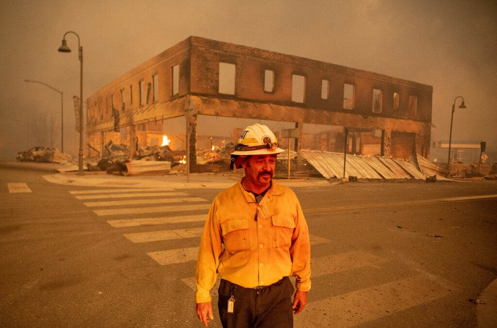 Battalion Chief Sergio Mora looks on as the Dixie fire burns through downtown Greenville, California on Aug. 4, 2021. Credit: Josh Edelson/AFP via Getty Images