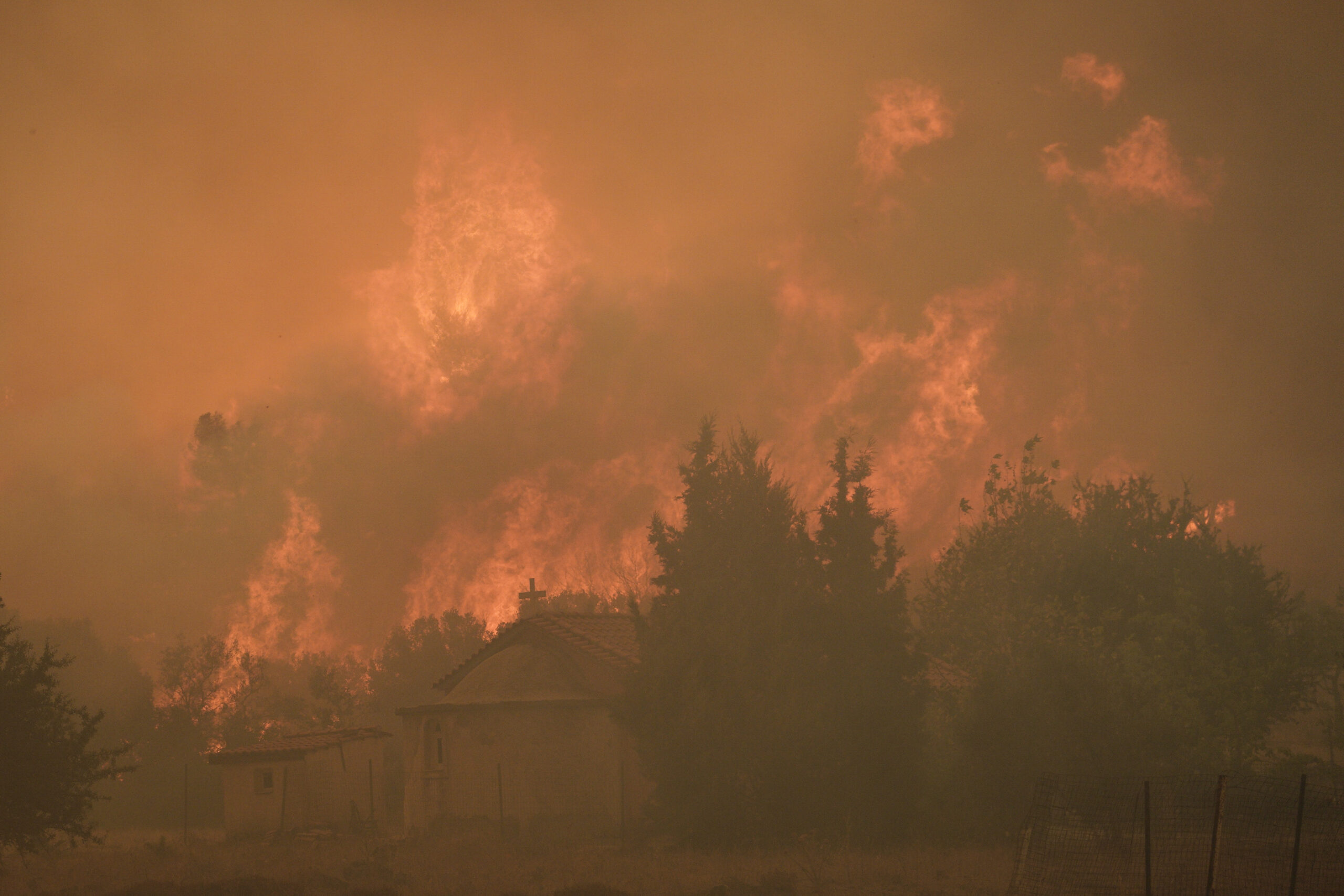 Smoke and flames rise as firefighters, locals and volunteers try extinguish a wildfire, near Vilia Village, Western Athens, Greece, on Aug. 18, 2021. Credit: Nick Paleologos/Anadolu Agency via Getty Images